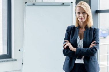 beautiful confident businesswoman standing with crossed arms and smiling at camera in office
