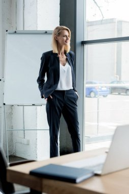 stylish blonde businesswoman standing with hands in pockets and looking at window