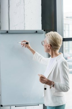 professional businesswoman in eyeglasses writing on whiteboard in office