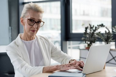 beautiful senior businesswoman in eyeglasses looking at camera while using laptop at workplace
