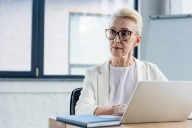 serious senior businesswoman in eyeglasses using laptop and looking away in office