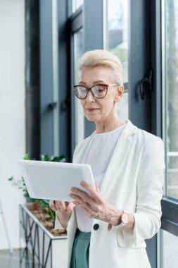 attractive senior businesswoman in eyeglasses using digital tablet