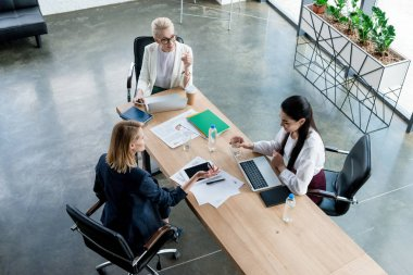high angle view of three professional businesswomen discussing project at workplace