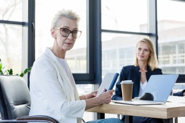 beautiful senior businesswoman looking at camera during meeting in office