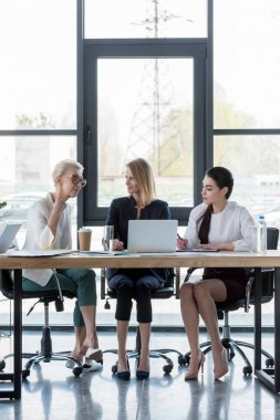 attractive businesswomen using laptop at meeting in office