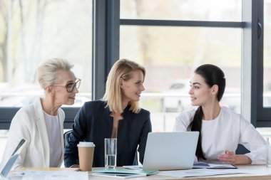 beautiful businesswomen looking at each other at meeting in office
