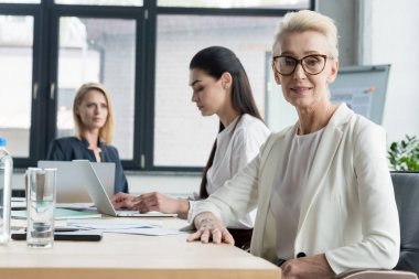 beautiful businesswomen sitting at table during meeting in office