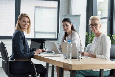 beautiful businesswomen sitting at meeting with gadgets in office