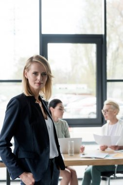 beautiful businesswoman standing in office and looking at camera