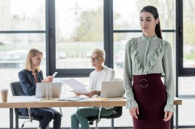 beautiful businesswoman standing in office and looking away