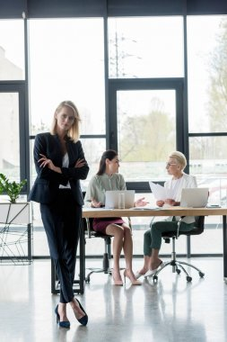 beautiful businesswoman standing with crossed arms at meeting in office