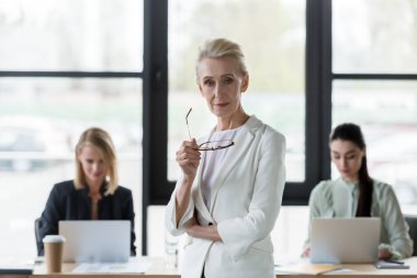 beautiful senior businesswoman holding glasses and looking at camera in office