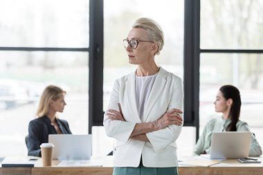 senior beautiful businesswoman standing with crossed arms in office