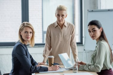 professional businesswomen looking at camera at meeting in office
