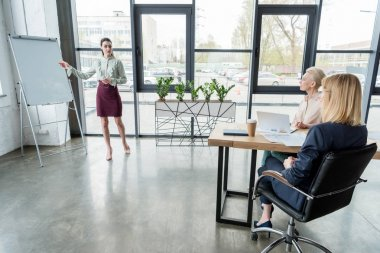 attractive businesswoman presenting project to colleagues at meeting in office