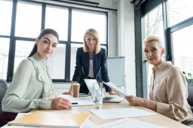 beautiful businesswomen looking at camera at meeting in office