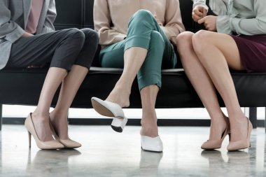 cropped image of three businesswomen sitting on sofa in office