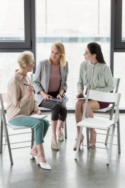 attractive businesswomen sitting on chairs and talking in office