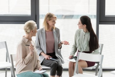 beautiful businesswomen sitting on chairs and talking in office