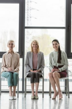smiling beautiful businesswomen sitting on chairs during meeting in office