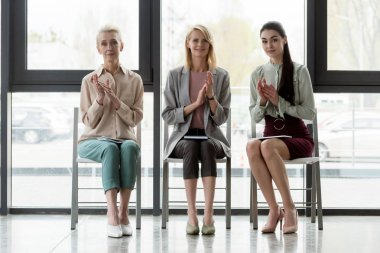 beautiful three businesswomen applauding in office