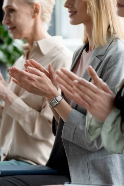 cropped image of businesswomen applauding during meeting in office