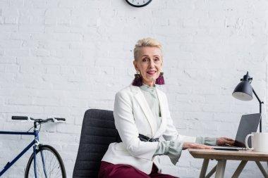 Smiling senior businesswoman using laptop in modern office stock vector