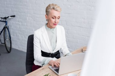 elegant senior business woman working with laptop in office