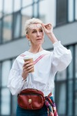 Fotografie stylish senior woman in trendy glasses holding disposable cup of coffee