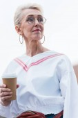 Fotografie attractive senior woman in fashionable outfit holding coffee to go