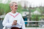 Fotografie beautiful senior woman in trendy outfit holding disposable cup of coffee in park