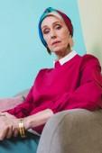elegantní starší žena v retro stylu, sedí v křesle