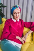 Módní starší žena sedí na žluté pohovce v retro stylu