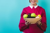 Fotografie cropped view of smiling senior woman with fresh fruits, isolated on blue