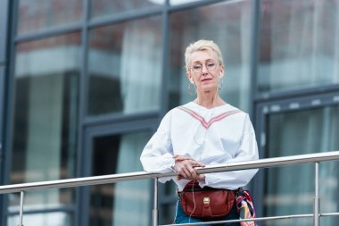 senior woman in trendy outfit listening music with earphones and standing near railings in urban city
