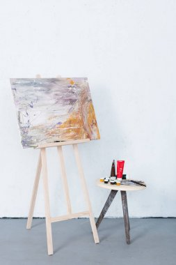 Painting on easel and paints on stool in creative workshop stock vector