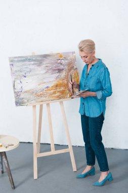 Senior female artist painting in workshop stock vector