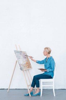 senior female artist painting with brush in workshop