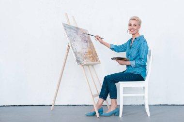 smiling senior female artist painting on easel in workshop