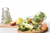 Detailní pohled krájecí desky, struhadlo, mísa, jablka, mrkev, brokolice a květák na stole izolovaných na bílém pozadí