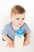 Fotografie high angle view of little boy with bottle of milk and sitting in highchair isolated on white background