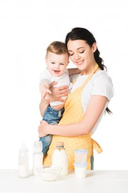happy mother in apron holding baby boy at table with children food isolated on white background