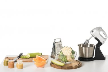 cutting boards, vegetables, grater, blender and bowl with cauliflower isolated on table