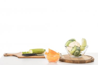 closeup view of cutting boards, knife, bowls, zucchinis, pumpkin and cauliflower on table isolated on white background