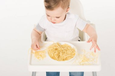 high angle view of baby boy sitting in highchair and eating spaghetti by hands