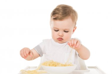 adorable child eating spaghetti by hands and sitting in highchair isolated on white background