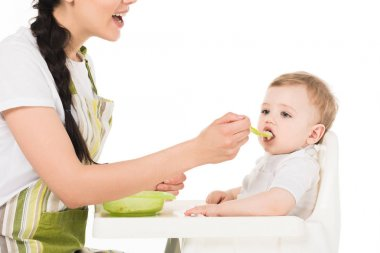 cropped shot of mother feeding little son sitting in highchair isolated on white background