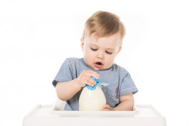 Little boy trying to open bottle of milk and sitting in highchair isolated on white background stock vector