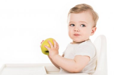 baby boy eating apple and sitting in highchair isolated on white background