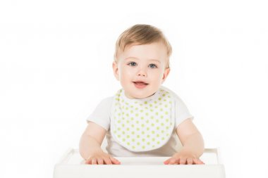 Smiling baby boy in bib sitting in highchair isolated on white background stock vector